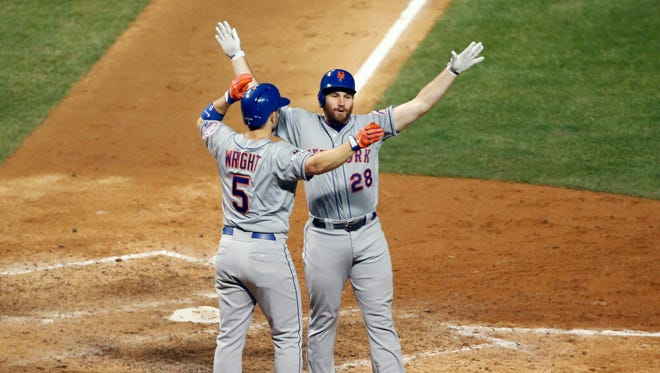 New York Mets second baseman Daniel Murphy (28) celebrates with third baseman David Wright (5) his two run home run in the eighth inning against the Chicago Cubs in game four of the NLCS at Wrigley Field.