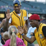 From left, Indiana Pacer Paul George and radio host Amp Harris high fives siblings of the late Caroline Symmes, Natalie and Sullivan Symmes, after they ran the bases during the Caroline Symmes celebrity softball challenge at Victory Field, Indianapolis, Thursday, June 9, 2016.