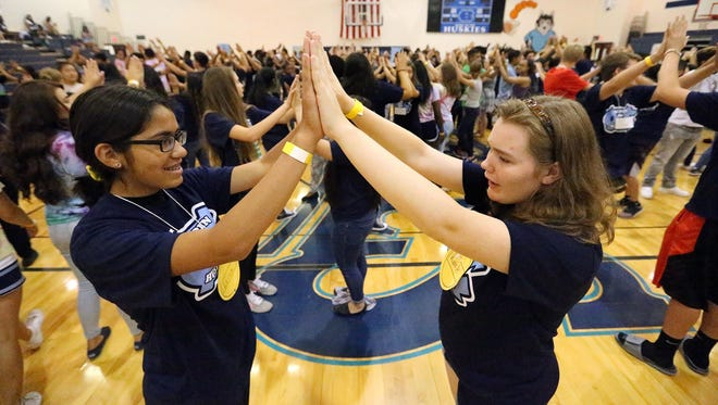 Laura Soto, left, and Kiana Hickey join hands during a get-acquainted exercise at Chapin High School's Fishing Freshmen Camp for incoming freshman Friday in the school's gymnasium. When doors open Monday, the Northeast school is expecting an influx of about 540 new students.