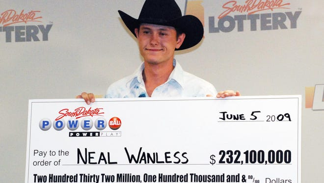 Neal Wanless  accepts a ceremonial check for winning a $232 million Powerball lottery jackpot in 2009.