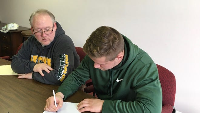With his dad watching, Zac Denton, right, signs his walk-on agreement to play football for Norfolk State next season. The Wilson Memorial graduate spent this past season at the Georgia Prep Sports Academy.