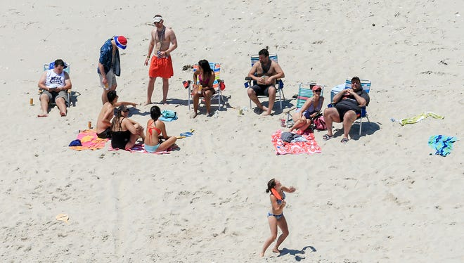 In this July 2 photo, Gov. Chris Christie, right, relaxes with his family and friends at the governor's summer house at Island Beach State Park. In a poll of New Jerseyans, 86 percent of the respondents had seen the beach photos.