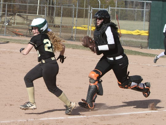 Brighton catcher Alexa Lamoreaux has Howell's Maddy Heilner in a rundown between home plate and third base. Heilner made it back to third safely.