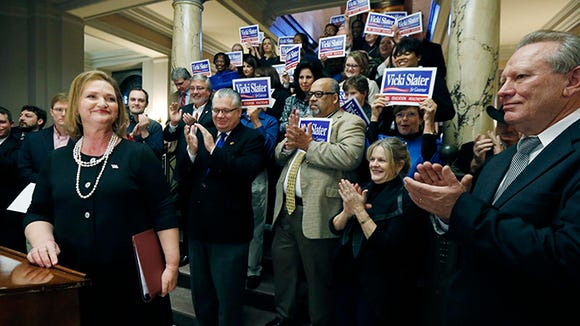 Madison, Miss. attorney Vicki Slater, left, looks at her husband, Scott Slater, right, after announcing her campaign for the Democratic Party nomination for governor at the Capitol in Jackson, Miss., Thursday, Feb. 19, 2015 Feb. 27 is the deadline for candidates to qualify for this year's election.