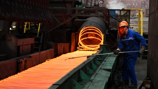 A worker manipulates coils of steel at Xiwang Special Steel in Zouping County in eastern China's Shandong province.