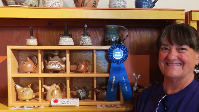 """Letha Cress Woolf is shown with her array of  """"Pinky Pots""""  that was awarded the blue ribbon in crafts at the Grant County Art Guild's Red Dot Art Show."""