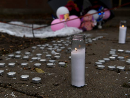 Candles burn around a roped off area where 16-year-old Deberianah Begley was shot and killed at the James Cayce Public Housing  in Nashville, Tenn., Wednesday, Oct. 11, 2017.