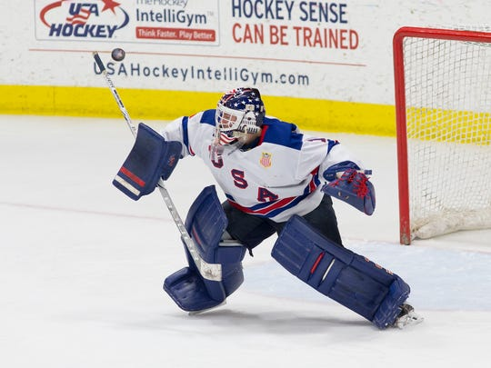 Maintaining sharp focus as he knocks a shot away with the knob of his goalie stick is Team USA's Dylan St. Cyr.