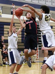 Pinckney's Dylan Reason splits Hartland defenders Denton Paul (left) and Jonathan Jackson (right) to score the game-tying basket with 3.9 seconds left in the fourth quarter.