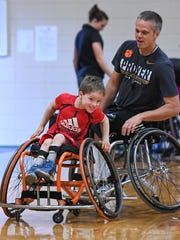 Seven-year-old Hudson Tucker tries to get away from coach Jeff Townsend during a game of tag at St. Matthew United Methodist Church in Greenville on Thursday, March 2, 2017. The game was to help kids taking part in a new wheelchair basketball team improve their strength and agility in the chairs used for the game.