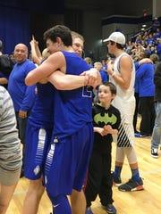 Scott senior Jake Ohmer, facing left, hugs sophomore