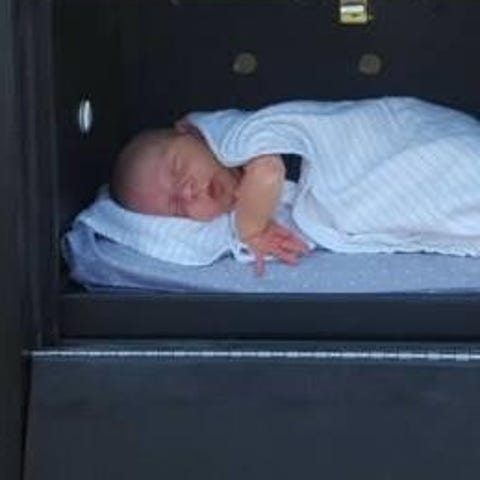 """An infant rests inside a """"baby box"""" installed in..."""