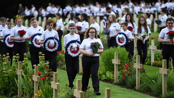 Youth arrive with flowers during a ceremony commemorating