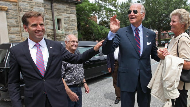 Vice President Joe Biden talks with Marcia Raniere after attending the funeral of the late Rev. Roberto Balducelli, at St. Anthony of Padua Parish, Tuesday, Aug.  13, 2013, as his son Attorney General Beau Biden stands nearby.