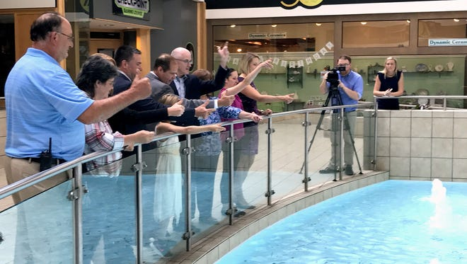 Arnot Mall and United Way officials toss coins into the center court fountain Thursday to celebrate more than $342,000 in coins thrown into the fountain over 25 years that have supported the United Way of the Southern Tier.