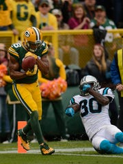 Green Bay Packers receiver Randall Cobb (18) scores on a 3-yard reception past Carolina Panthers cornerback Charles Godfrey (30) in the second quarter during Sunday's game at Lambeau Field.