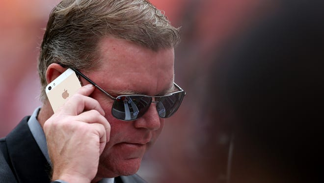 General manager Scot McCloughan of the Washington Redskins talks on the phone prior to the start of a game against the St. Louis Rams on Sept. 20 in Landover, Md.