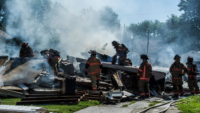 Evansville firefighters tear apart the remains of a charred house at 1717 Hercules Ave. in Evansville, Ind., on Tuesday, June 27, 2017. The house explosion, which was reported at 8:45 a.m., injured at least three people.