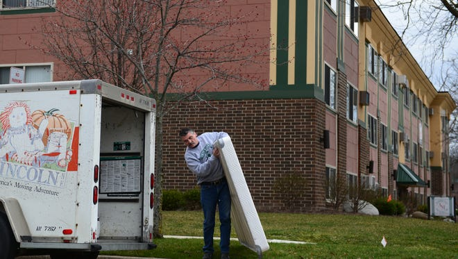 Rich Spooner helps move a mattress out of Carley Spooner's apartment on Wednesday, March 30, 2016 at Abbot Manor in East Lansing after the City of East Lansing deemed the complex unsafe. As many as 51 people are being forced to move out. Rich, her father, drove with her mother from Adrian to help her move.