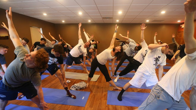 Yoga instructor Erica Denman, center, works with the Webster Thomas boys lacrosse team.