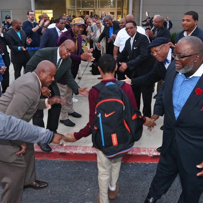 About 70 men from the community lined the walkway leading