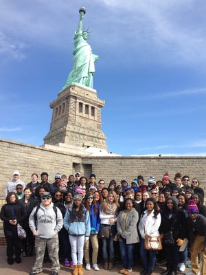 Area students and chaperones pose at the Statue of Liberty.