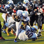 Titusville High's Jaleel Davis scores a touchdown up the middle on a host of Palm Bay High defenders.