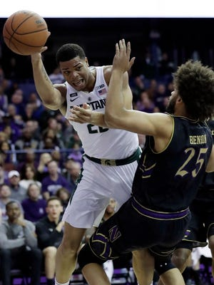 Michigan State guard/forward Miles Bridges, left, passes against Northwestern center Barret Benson during the first half on Saturday, Feb. 17, 2018, in Rosemont, Ill.