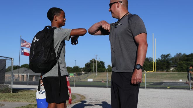Football coach Bob Wager, right, and sophomore safety Cameron Conley greet each other Thursday at the re-opening of strength and conditioning camp at Arlington Martin High School in Arlington, Texas. The team suspended workouts after a layer tested positive for COVID-19.