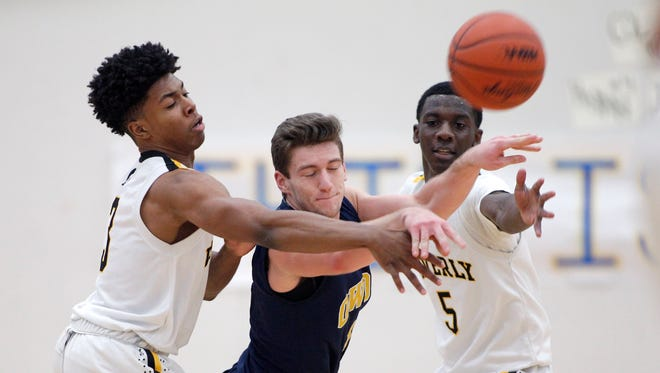 Waverly's Bryson Fronta, left, and Keshaun Harris, right, pressure Owosso's Carson Bornefeld, as he makes a pass, Monday, March 5, 2018, in DeWitt, Mich.