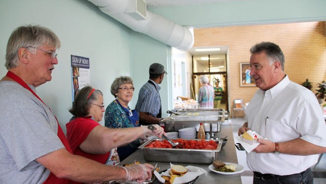 Volunteers at Black Mountain Open Table serve lunch to Sonny Loor, the manager for the Swannanoa Christian Valley Ministry's Homeless Shelter. Open Table serves a free meal to the community every Wednesday.