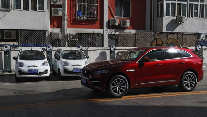 In this Friday, April 14, 2017 photo, a SUV vehicle drives past electric cars parked at a charging station outside a residential building in Beijing. Automakers face a dilemma in China, where regulators are pressing them to sell electric cars but consumers want gas-guzzling SUVs. This month's Shanghai auto show, the industry's biggest marketing event of the year, will showcase efforts to create electric models Chinese drivers want to buy. (AP Photo/Andy Wong)
