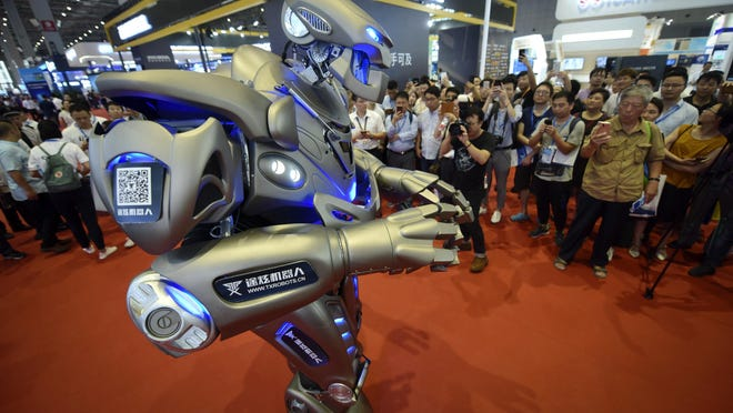 Visitors watch a robot performing at the China International Industry Fair in Shanghai, Wednesday, Sept. 19, 2018. China's No. 2 leader appealed Wednesday for support for free trade and promised to improve conditions for foreign companies following tit-for-tat U.S. and Chinese tariff hikes in an escalating battle over Beijing's technology policy. Premier Li Keqiang's comments add to Beijing's effort to portray itself as a defender of global trade and multilateralism in the face of complaints by Washington and other trading partners about industry policies they say violate its market-opening commitments. (Chinatopix via AP)