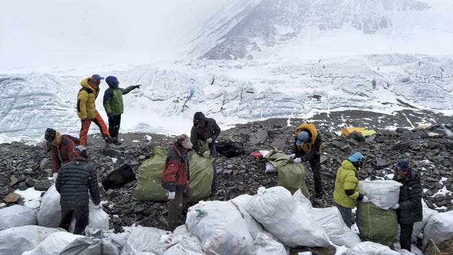In this May 8, 2017, file photo released by Xinhua News Agency, people collect garbage at the north slope of the Mount Qomolangma in southwest China's Tibet Autonomous Region. China announced that it plans to cut the number of climbers attempting to scale Mount Everest from the north by 1/3 this year as part of plans for a major cleanup on the world's highest peak.
