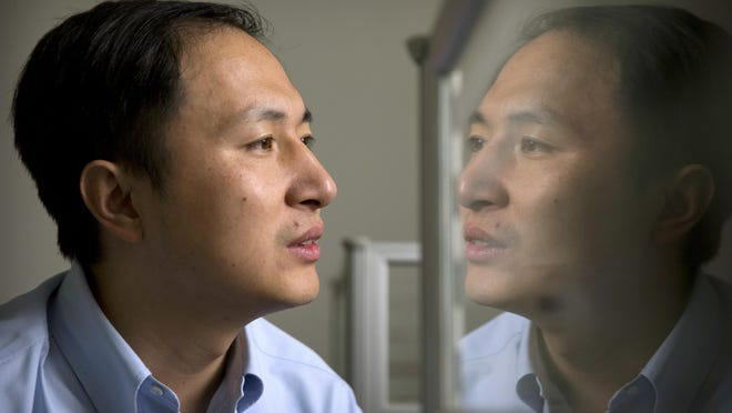 He Jiankui is reflected in a glass panel as he works at a computer at a laboratory in Shenzhen in southern China's Guangdong province.