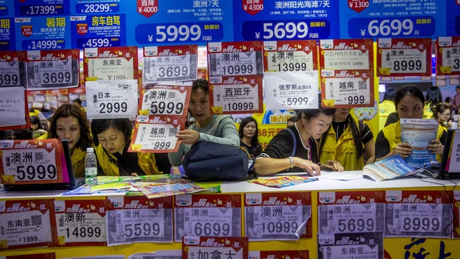 In this March 3, 2018, photo, people check on travel packages offered by travel agencies during the Guangzhou International Travel Fair in Guangzhou in south China's Guangdong province. Travelers in China were blocked from buying plane tickets 17.5 million times last year as a penalty for failing to pay fines or other offenses.