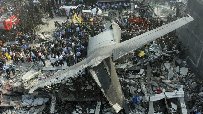 In this Tuesday, June 30, 2015 file photo, rescuers search for victims at the site where an Hercules C-130 air force cargo plane crashed into a residential neighborhood in Medan, North Sumatra, Indonesia.