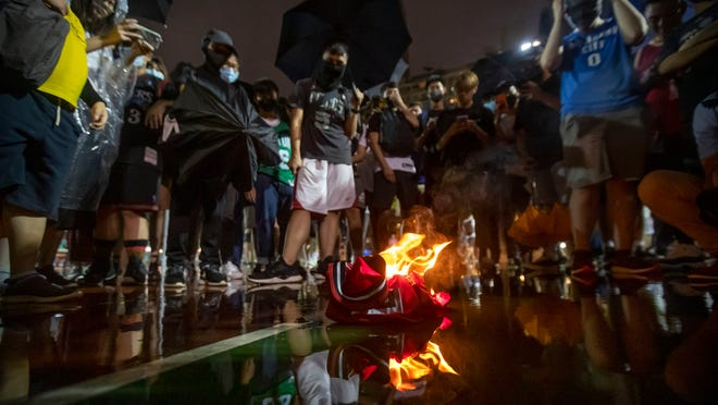 Demonstrators burn a Lebron James jersey during a rally in Hong Kong on Oct. 15. Protesters threw basketballs at a photo of James and shouted angry chants after the Los Angeles Lakers star made comments about free speech.