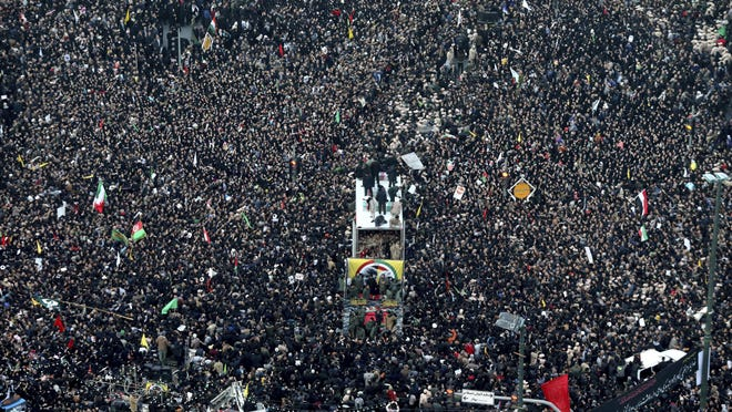 Coffins of Gen. Qassem Soleimani and his comrades who were killed in Iraq by a U.S. drone strike, are carried on a truck surrounded by mourners during a funeral procession, in the city of Mashhad, Iran, Sunday, Jan. 5, 2020. Soleimani's death Friday in Iraq further heightens tensions between Tehran and Washington after months of trading attacks and threats that put the wider Middle East on edge. (Mohammad Hossein Thaghi/Tasnim News Agency via AP)