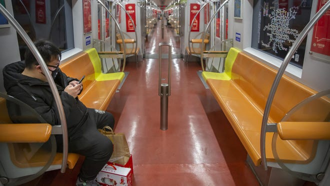 A man wearing a face mask rides a nearly empty subway train Sunday in Beijing. The new virus accelerated its spread in China, and the U.S. Consulate in the epicenter of the outbreak, the central city of Wuhan, announced Sunday it will evacuate its personnel and some private citizens aboard a charter flight.