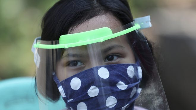 A child wears a face mask and shield as a precaution against the new coronavirus at a community health center in Tangerang, Indonesia.