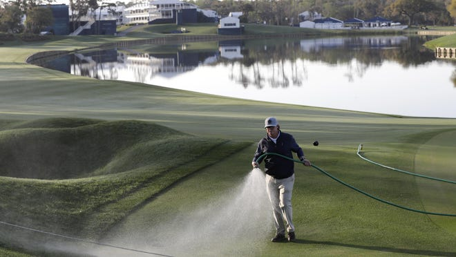A grounds crew worker waters the 18th green after the PGA tour canceled the rest of The Players Championship golf tournament as a result of the coronavirus pandemic, March 13, in Ponte Vedra Beach. Other tournaments have been shut down for the next three weeks.