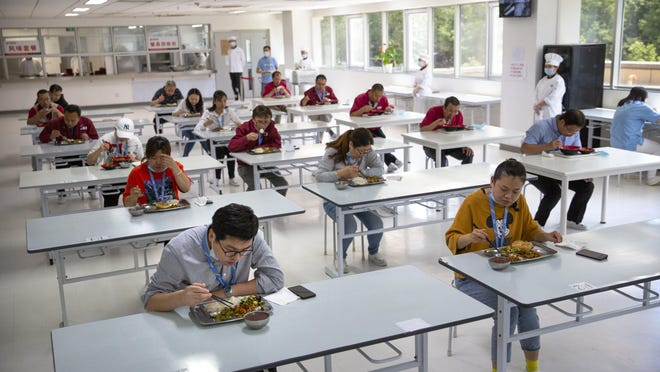 Employees practice social distancing while they eat lunch at a staff cafeteria in a semiconductor production facility for Renesas Electronics during a government organized tour for journalists in Beijing, Thursday, May 14, 2020. China reported three new coronavirus cases Thursday while moving to reopen for business and schools.