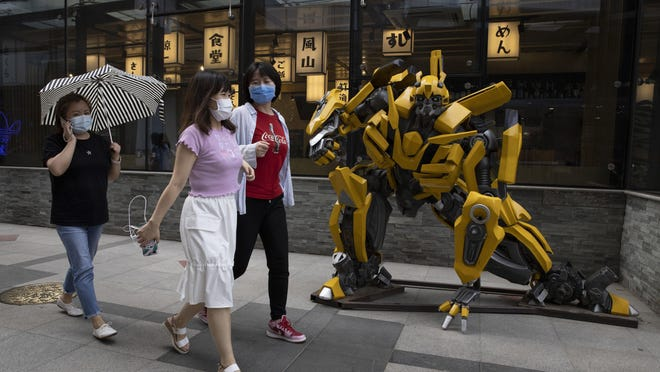 Residents wearing face masks to curb the spread of the coronavirus walk past a sculpture depicting a character from the Transformer movie outside a restaurant in Beijing on Monday, June 8, 2020. A semblance of normalcy has returned to the Chinese capital as businesses open and residents go about their usual activities.