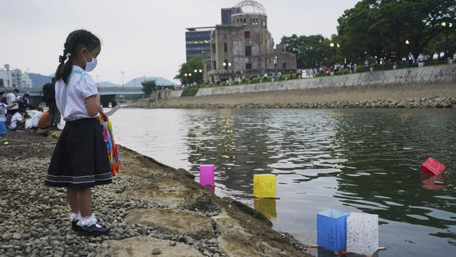 Saki Morioki, 5 years old, looks at paper lanterns floating along the Motoyasu River in front of the Atomic Bomb Dome, Thursday, Aug. 6, 2020. in Hiroshima, western Japan. Japan marked the 75th anniversary Thursday of the atomic bombing of Hiroshima. The official lantern event was cancelled to the public due to coronavirus but a small group of local representatives released some lanterns.