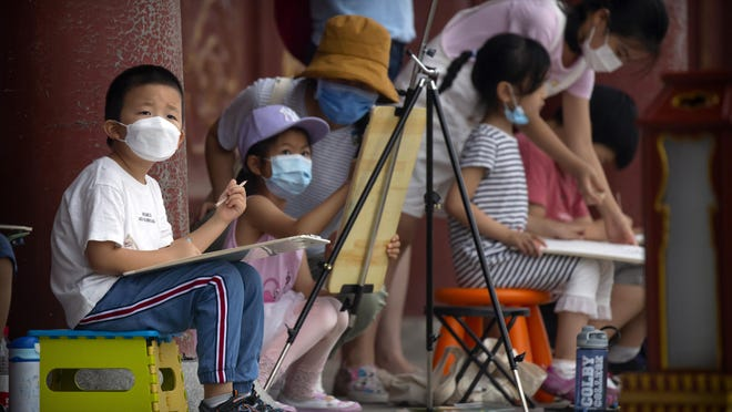Children wearing face masks to protect against the coronavirus sketch the Temple of Heaven on Saturday in Beijing. Authorities in a city in far western China have reduced subways, buses and taxis and closed off some residential communities amid a new coronavirus outbreak, according to Chinese media reports. They also placed restrictions on people leaving the city, including a suspension of subway service to the airport.