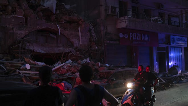 People ride past damaged buildings at a neighborhood without electricity near the scene of Tuesday's explosion that hit the seaport of Beirut, Lebanon, Friday, Aug. 7, 2020. Rescue teams were still searching the rubble of Beirut's port for bodies on Friday, nearly three days after a massive explosion sent a wave of destruction through Lebanon's capital, killing over a hundred people and wounding thousands.