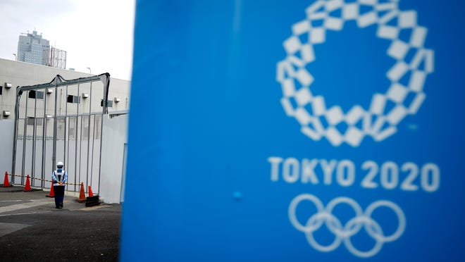 """In this May 12, 2020, file photo, a lone security guard stands at one of the venues for the Tokyo 2020 Olympic Games in Tokyo. The head of the Tokyo Olympics on Friday, June 12, 2020, says that 80% of the facilities needed for next year's games have """"basic approval""""to be used."""