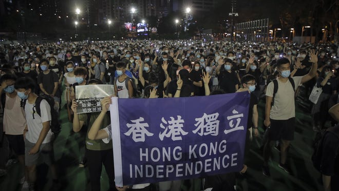 """Participants gesture with five fingers, signifying the """"Five demands - not one less"""" and showing a banner read """" Hong Kong Independence"""" during a vigil for the victims of the 1989 Tiananmen Square Massacre at Victoria Park in Causeway Bay, Hong Kong, Thursday."""