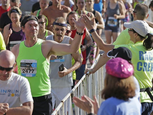 Michael Meives gets a high five as his corral moves into the start area of the Bellin Run in Green Bay.